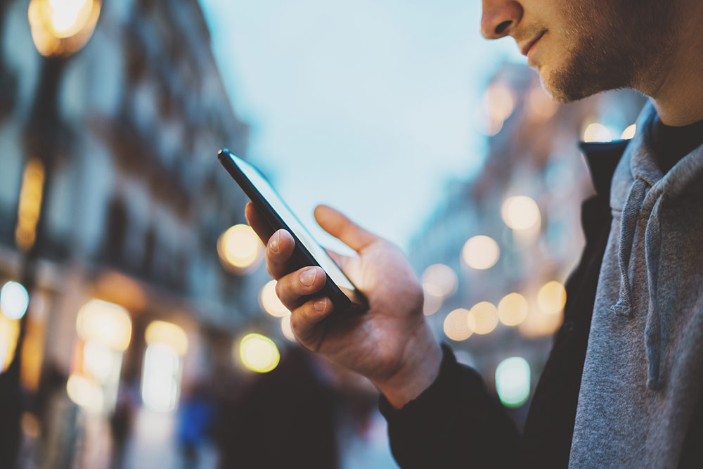 Man outside looking at smartphone