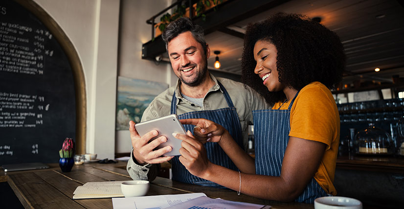Small business owner and employee looking at tablet and smiling