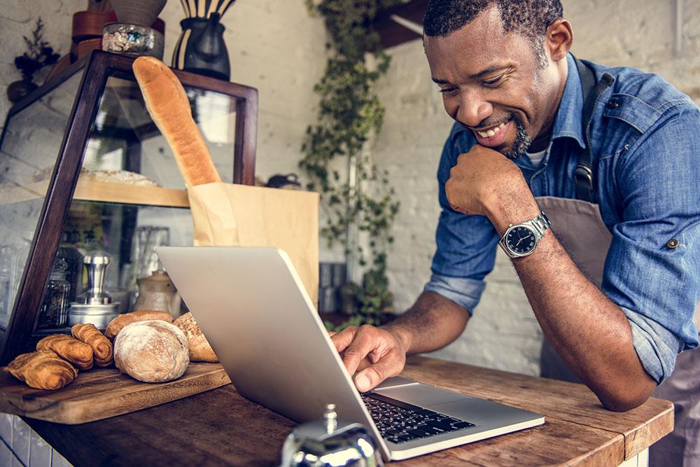 Baker on laptop in shop smiling