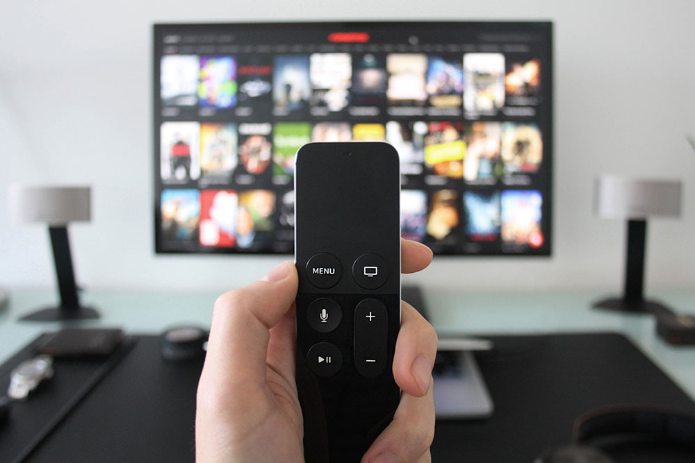 Close up of person holding remote with tv on in background with Netflix menu on screen