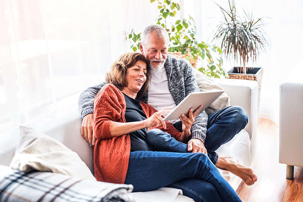 Senior couple sitting on couch looking at tablet