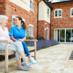 Senior woman sitting with caregiver in senior community sitting on bench