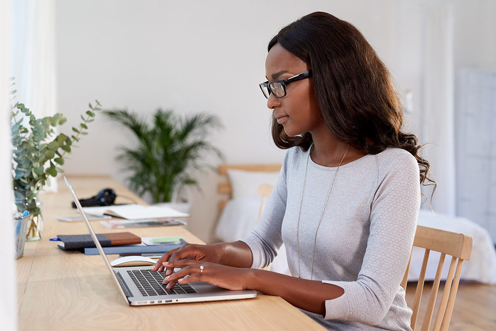 Woman sitting at table typing on laptop