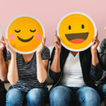 People sitting with emojis covering faces