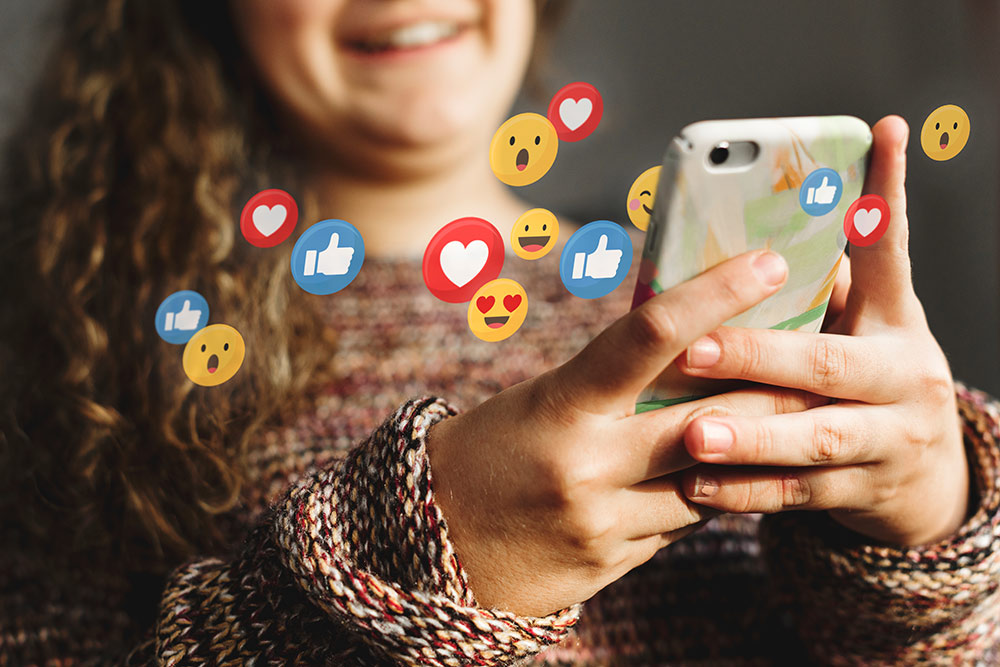 Woman on smartphone smiling while checking social media with emojis around her